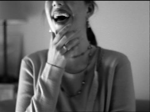vídeos de stock, filmes e b-roll de b/w slow motion close up portrait seated young woman laughing + covering mouth with hand indoors - mãos cobrindo boca