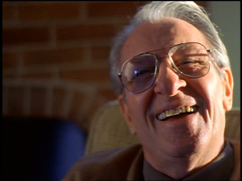 slow motion close up PORTRAIT senior man with eyeglasses sitting in chair indoors laughing