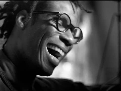 b/w slow motion close up portrait young black man with dreadlocks + eyeglasses laughing indoors - dreadlocks stock videos & royalty-free footage