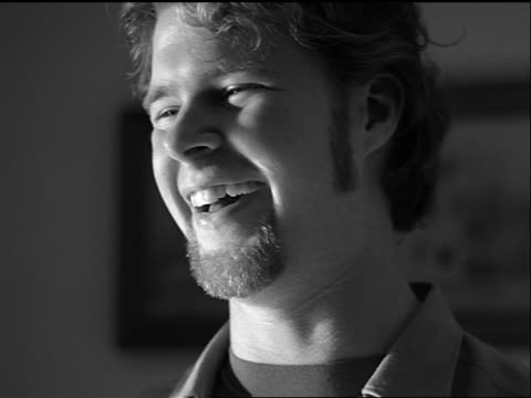 b/w slow motion close up portrait young man with goatee laughing + shaking head indoors - goatee stock videos & royalty-free footage