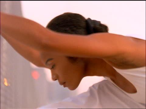 vidéos et rushes de slow motion close up profile black woman in white stretching head towards knees / nyc - image animée