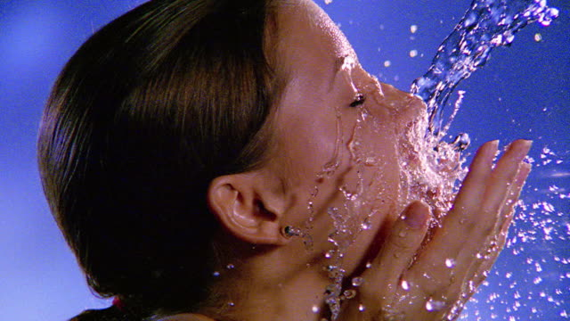 slow motion close up PROFILE water pouring onto woman's face from above