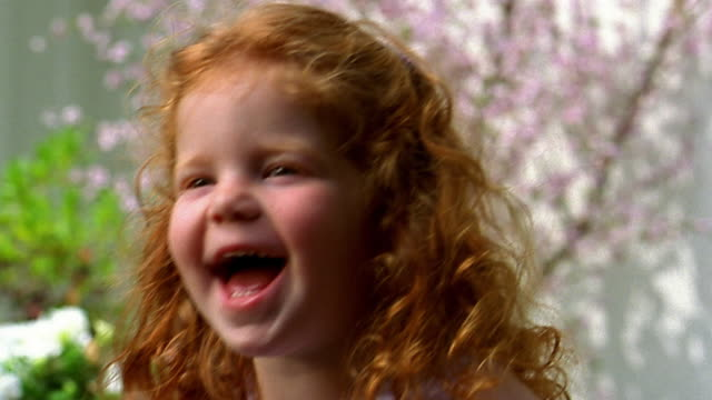 Slow motion close up rack focus small redhead girl laughing