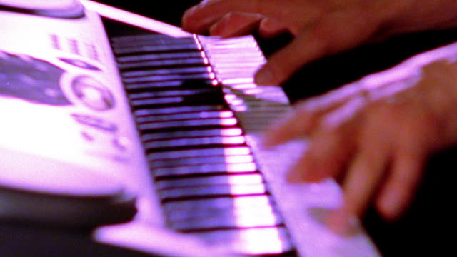high contrast overexposed slow motion close up rack focus zoom out zoom in hands of man playing electronic keyboard - synthesizer stock videos & royalty-free footage