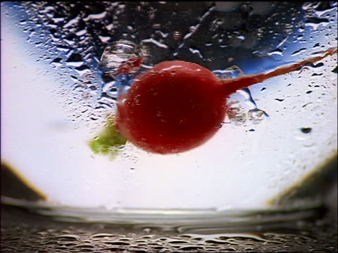 slow motion close up red radish falling into glass bowl of water - crucifers stock videos & royalty-free footage