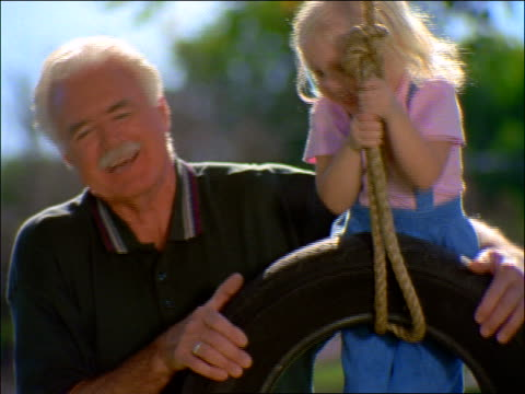 slow motion close up senior man pushing granddaughter on tire swing - tyre swing stock videos & royalty-free footage