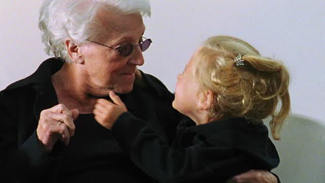 vídeos de stock, filmes e b-roll de slow motion close up senior woman in sunglasses + girl dressed in black with white background / girl kisses senior woman - mãos cobrindo boca
