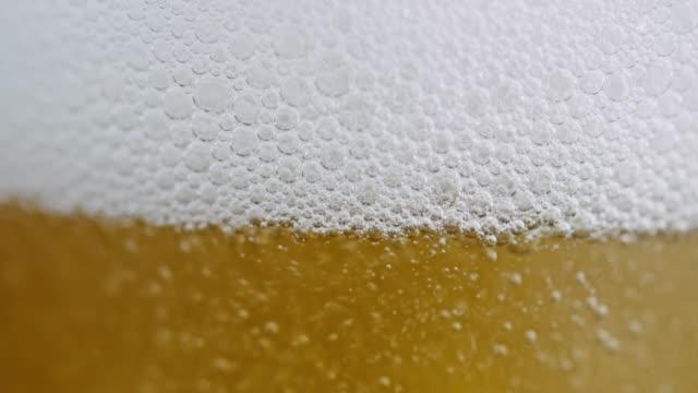 vídeos de stock, filmes e b-roll de câmera lenta perto tiro de derramar cerveja com bolhas e espuma em um copo - encher