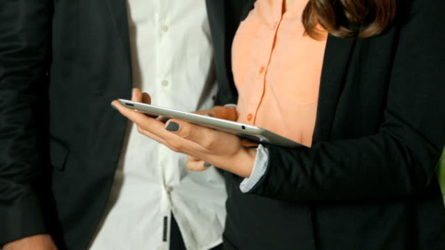 Slow motion close up shot of two office workers discussing a business project using a tablet