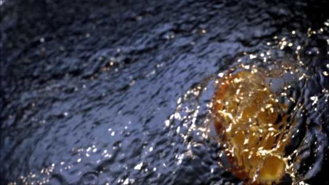 Slow motion close up slice of orange flying through splash of water