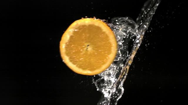 slow motion close up slice of orange flying through splash of water - orange stock videos & royalty-free footage