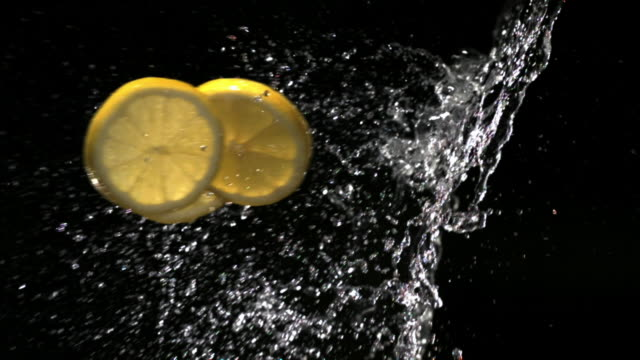 Slow motion close up slices of lemon flying through splash of water