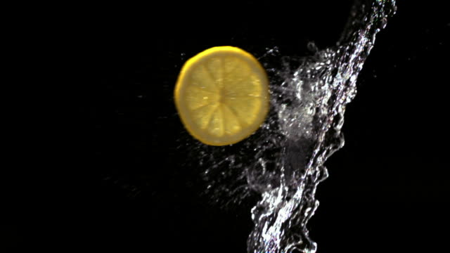 slow motion close up slices of lemon flying through splash of water - レモン点の映像素材/bロール