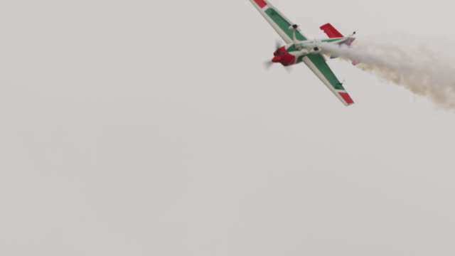 slow motion close up small prop plane loses control, drops spinning into a free-fall, trailing smoke. - acrobatica aerea video stock e b–roll