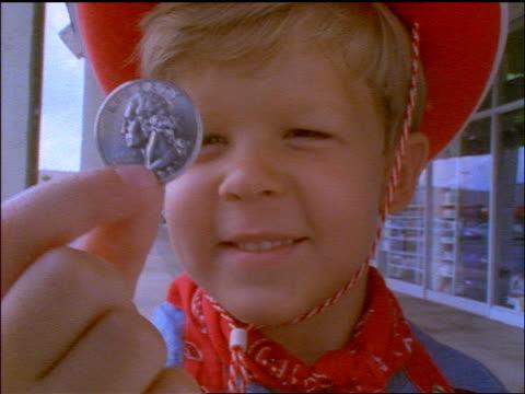 vidéos et rushes de slow motion close up smiling blonde boy wearing cowboy hat + holding up quarter in front of camera - tête composition