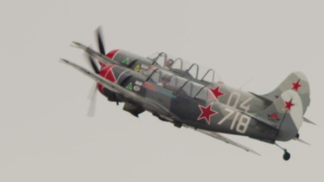 slow motion close up soviet yak-52 two military propeller aircraft fly in tight formation past camera and trail smoke. - united states airforce stock-videos und b-roll-filmmaterial