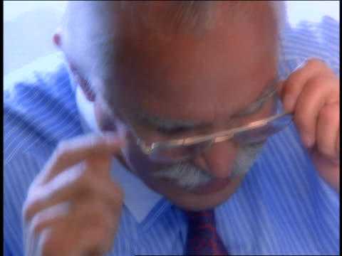 slow motion close up stressed senior businessman removing eyeglasses + holding head in hands - solo un uomo anziano video stock e b–roll
