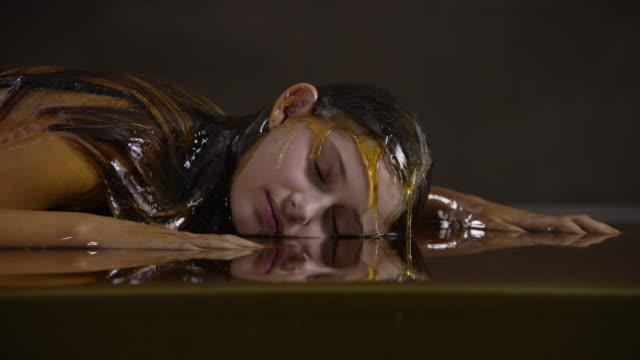 slow motion close up, teenage girl lies in honey - one teenage girl only点の映像素材/bロール