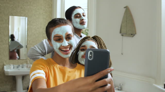 slow motion close up, teenagers with facemask take selfie in bathroom - メイクアップブラシ点の映像素材/bロール