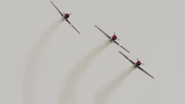 slow motion close up three soviet yak-52 military propeller aircraft fly in tight formation directly toward camera trail smoke. - acrobatica aerea video stock e b–roll