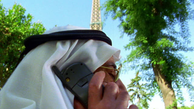 slow motion close up tilt down arab man in headdress talking on cell phone turning to camera with eiffel tower in background - headdress stock videos & royalty-free footage