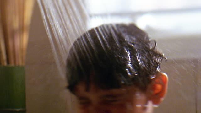 Slow motion close up tilt down boy washing face under shower