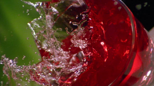 slow motion close up tilt down ice cube falling in to red drink + splashing