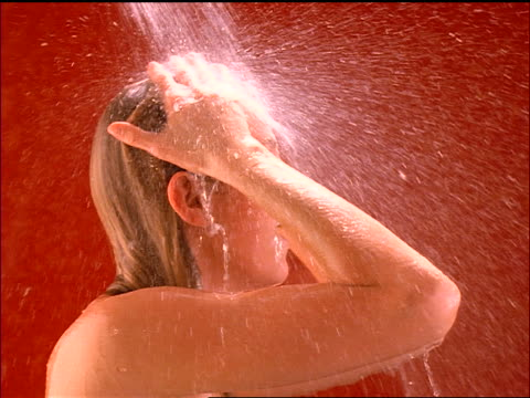 slow motion close up tilt down profile woman washing hair in shower / red background - washing hair stock videos & royalty-free footage