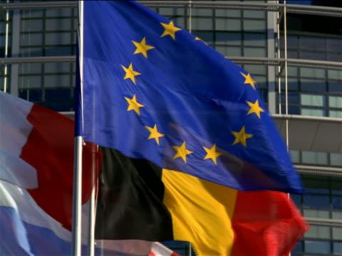 vidéos et rushes de slow motion close up tilt down tilt up eu flag + others / weiss eu parliament building in background / strasbourg, france - bâtiment du parlement