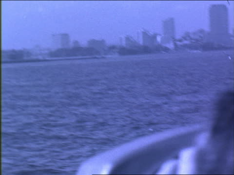 b/w blue slow motion close up tilt up from woman on ferry looking through public telescope to statue of liberty - statue of liberty new york city stock videos & royalty-free footage