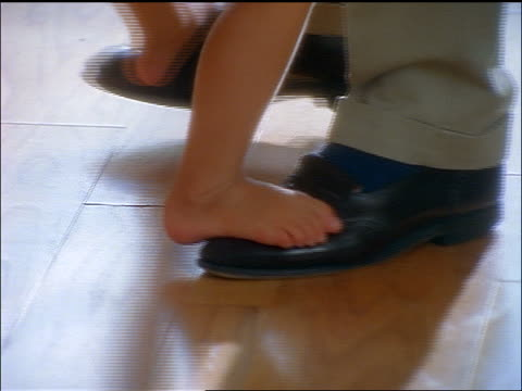 slow motion close up tilt up little girl dancing barefoot on father's feet indoors