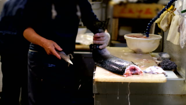 4k slow motion: close up to hand of professional fishermen preparing salmon fish by slice and cutting at fish market - fish market stock videos & royalty-free footage