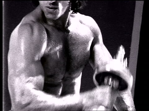 b/w slow motion close up torso of sweaty barechested man lifting dumb bells outdoors - ハンドウェイト点の映像素材/bロール