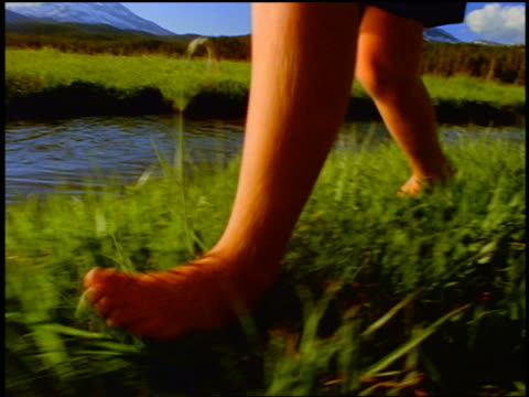 slow motion close up tracking shot bare legs of boy running in grass by stream / Sparks Meadow, Cascade Mountains, Oregon