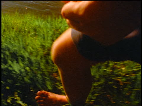 vídeos de stock, filmes e b-roll de slow motion close up tracking shot bare legs of boy running in grass by stream / sparks meadow, cascade mountains, oregon - barefoot