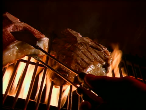 slow motion close up tracking shot of hand with tongs turning steak on grill - steak stock videos and b-roll footage