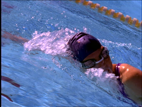 slow motion close up tracking shot of woman swimming crawl stroke in race