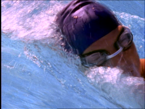 stockvideo's en b-roll-footage met slow motion close up tracking shot of woman swimming crawl stroke in race - buitenbad