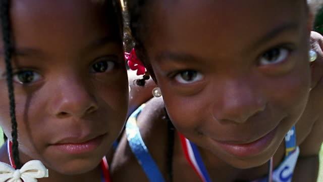 slow motion close up twin small black girls posing - そっくりさん点の映像素材/bロール
