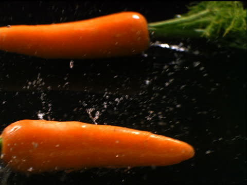 vídeos y material grabado en eventos de stock de slow motion close up two carrots sliding past on water covered black surface - enfoque de objetos sobre la mesa