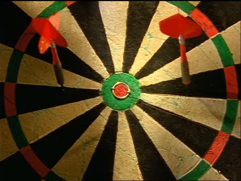 slow motion close up two darts hitting dart board with one dart already there / one dart hits bullseye - ダーツ点の映像素材/bロール