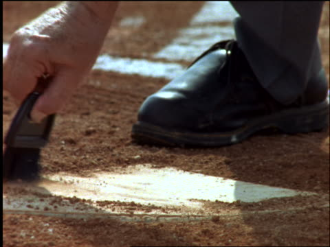 slow motion close up umpire's hand brushing dirt off home plate - baseball diamond stock videos and b-roll footage