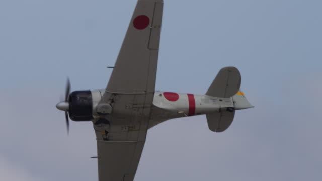 Slow motion close up vintage Japanese A6M Zero military prop plane flies through the sky.
