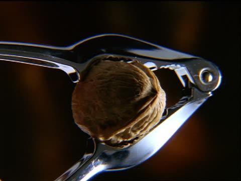 stockvideo's en b-roll-footage met slow motion close up walnut being cracked by nutcracker - notendop