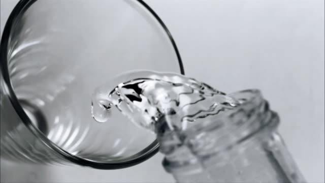Slow motion close up water being poured into glass