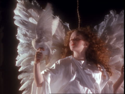 slow motion close up woman angel in white holding white dove flapping its wings / wind blowing