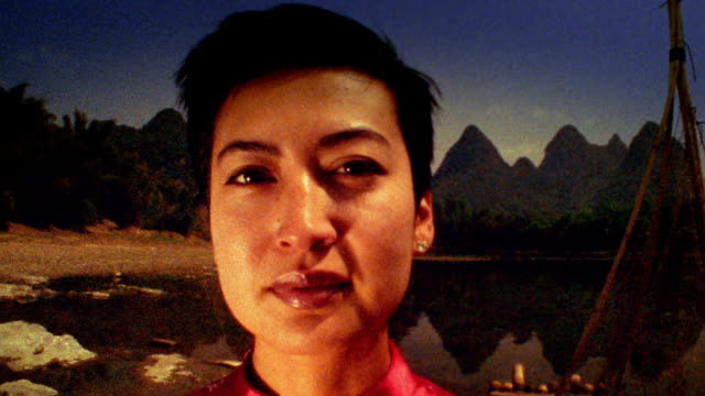 vidéos et rushes de slow motion close up woman in red dress standing with river and mountains in background / china - robe rouge