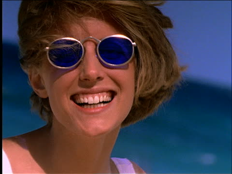slow motion close up woman in sunglasses and swimsuit measuring waist