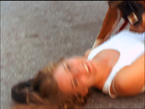 slow motion close up woman lying on ground as dog stands over her licking her face