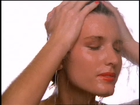 slow motion close up woman rubbing head + smiling in shower - 人の髪点の映像素材/bロール